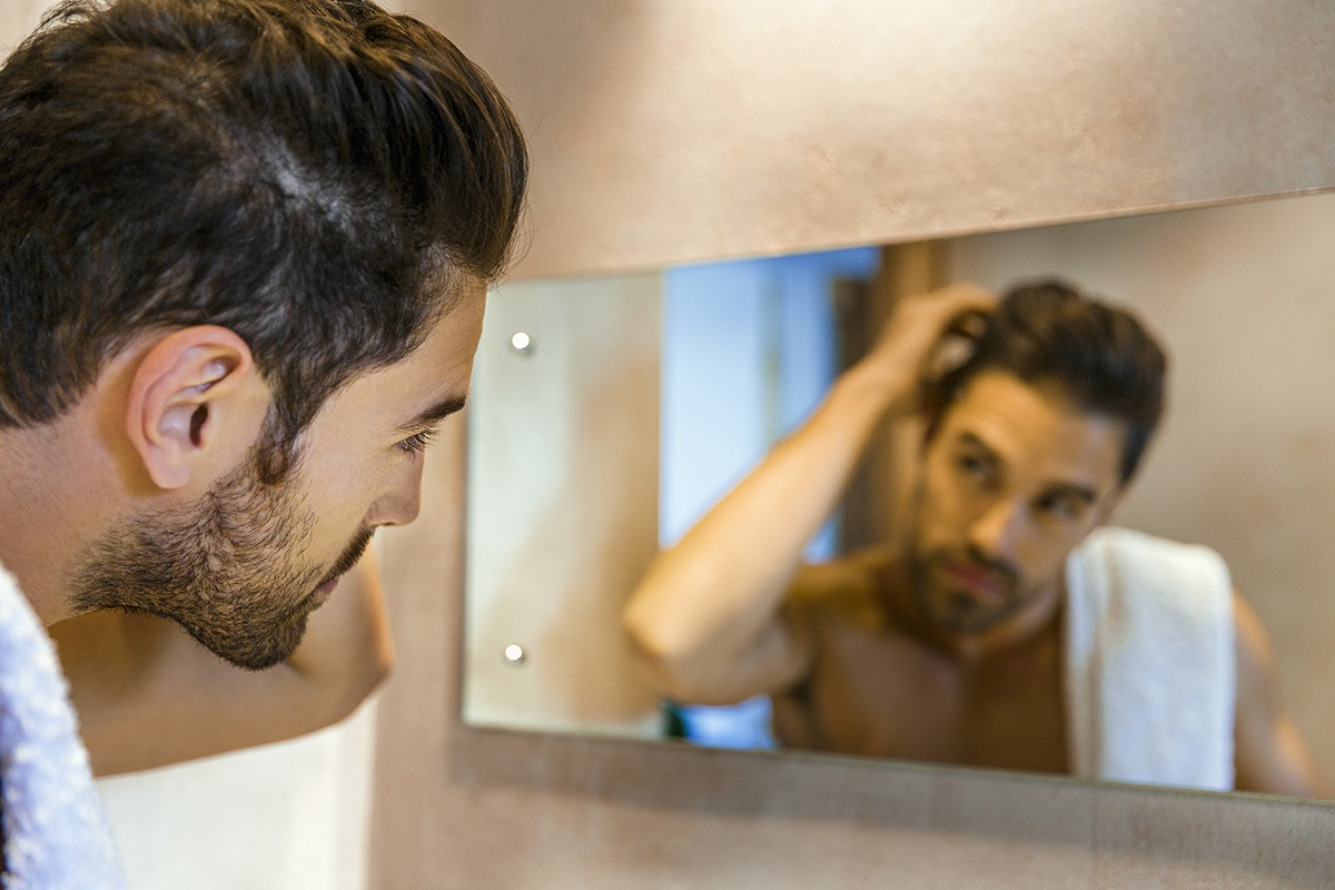 Man examining hair in mirror